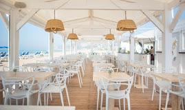 Restaurante acogedor, disfruta de un chiringuito diferente, de su decoración en tonos blancos y cámel que se funden con el entorno. Descubre una exquisita oferta gastronómica acompañada de buena música y el mejor ambiente.