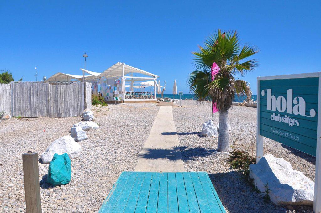 """Hola Beach Club és un espai únic i singular. Flanquejat pel club de golf Terramar, el nostre beach club gaudeix d'una màgia i un encant que el fan únic a la comarca. En ell podràs gaudir des d'un bany de sol a les seves còmodes hamaques, degustar una de les seves """"tapes d'autor"""" o gaudir de la música d'alguns dels millors DJ del panorama nacional. En definitiva un lloc màgic on desconnectar del món per connectar amb un mateix."""